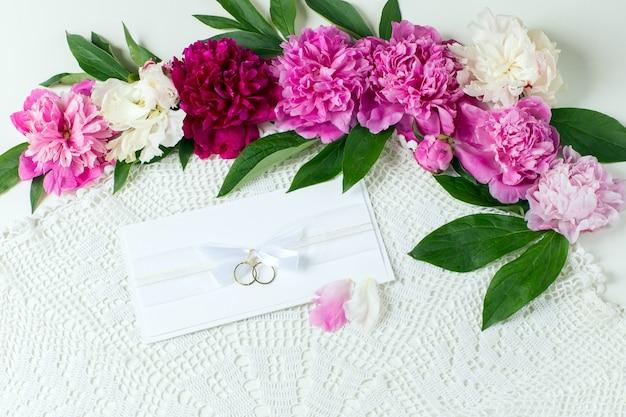 Botões de peônias, cartão com anéis de casamento