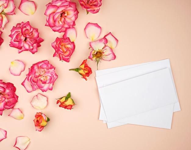Botões de rosa amarela e um envelope de papel branco sobre um fundo de pêssego