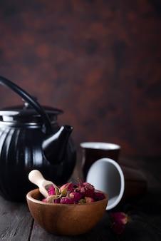 Botões de rosa chá na tigela de madeira com bule de chá