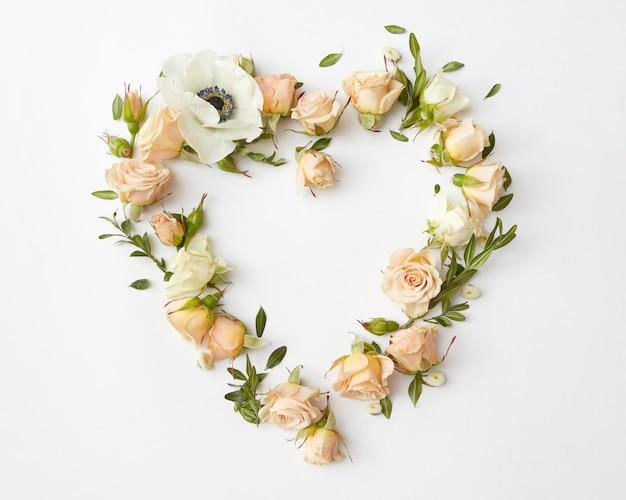 Botões de rosas bege dispostos em forma de coração em fundo branco, camada plana