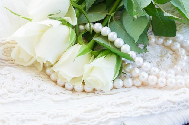Botões de rosas frescas brancas com joias de rendas e pérolas