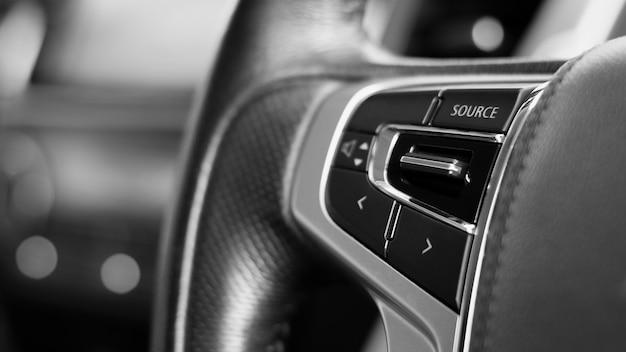 Botões multifuncionais para controle rápido em um volante preto.