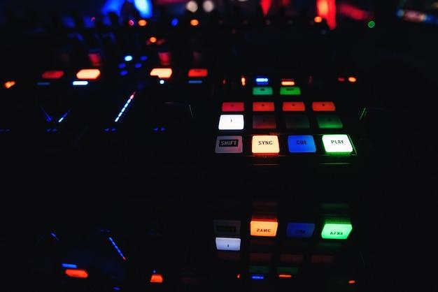 Botões no mixer dj com iluminação para criar e misturar música com um escuro