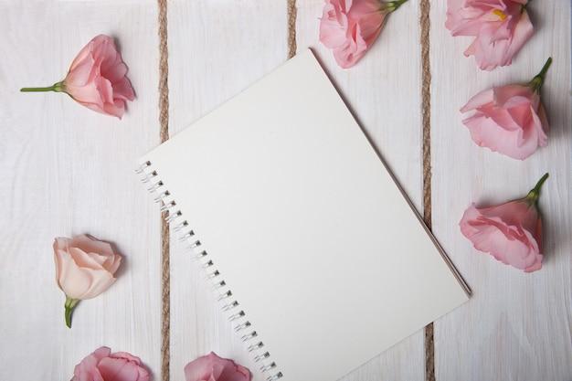 Botões rosa eustomas mentem em torno do livro de papel branco sobre fundo claro de madeira