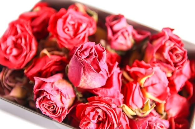 Botões secos de rosa vermelha, flores e pétalas na caixa de papelão aberta