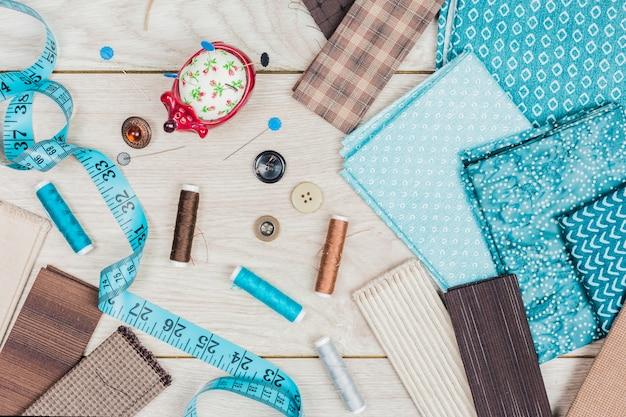 Botões; um conjunto de agulhas; bobinas de fio são necessárias para costurar roupas na mesa de madeira