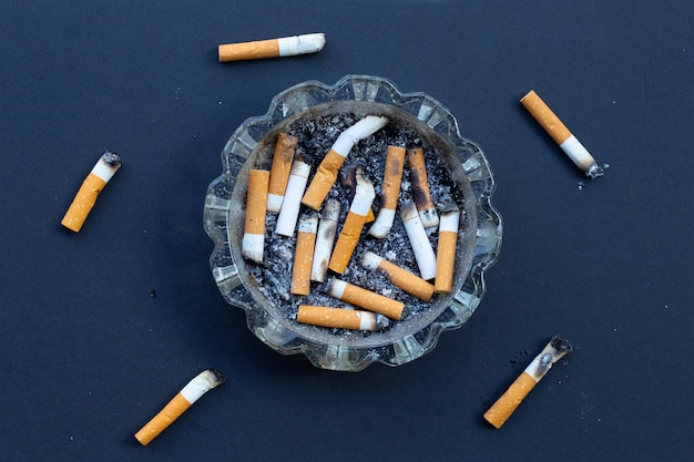 Botos de cigarro sujos na mesa preta.