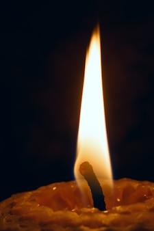 Bougie iluminado em close up de fundo escuro.