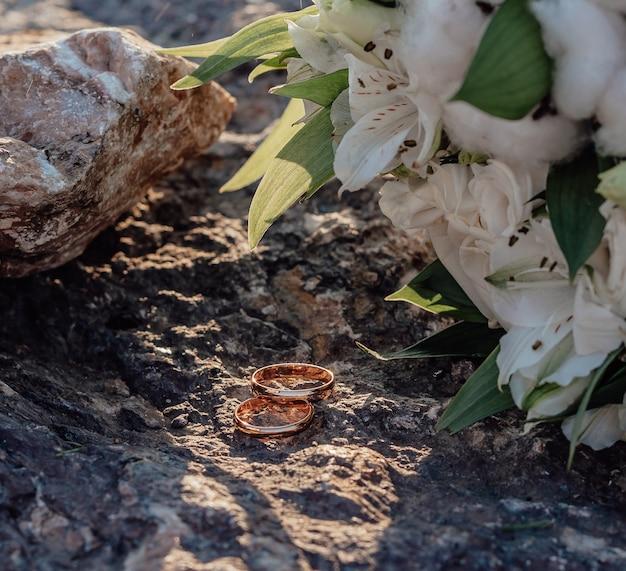Bouquet com linda alstroemeria branca e algodão e alianças em um fundo de pedra