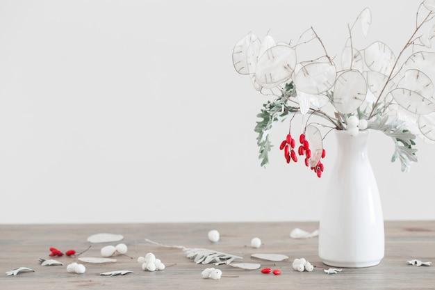 Bouquet com lunaria e frutas vermelhas em um vaso branco na mesa de madeira