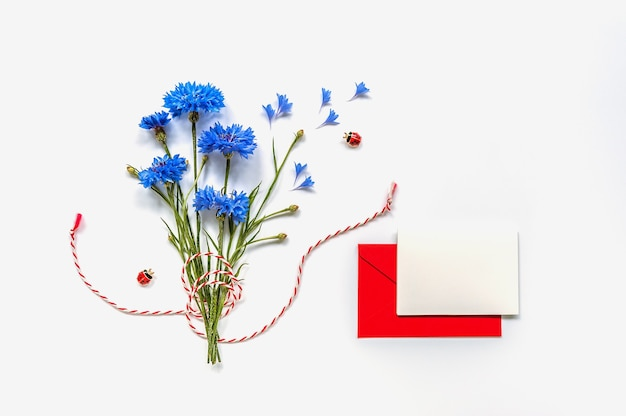 Bouquet de delicadas flores com cartão postal em branco e envelope vermelho na superfície branca. espaço para texto. foco suave. vista do topo.