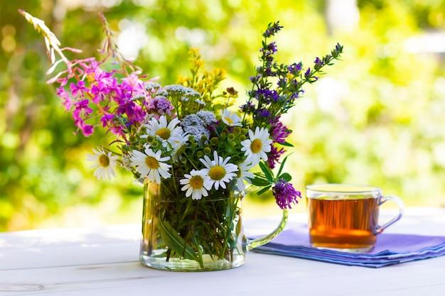 Bouquet de ervas medicinais frescas e uma xícara de chá de ervas