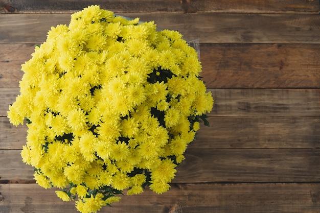 Bouquet de flores amarelas em fundo de madeira. dia de todos os santos. dia dos mortos. copie o espaço. vista do topo.