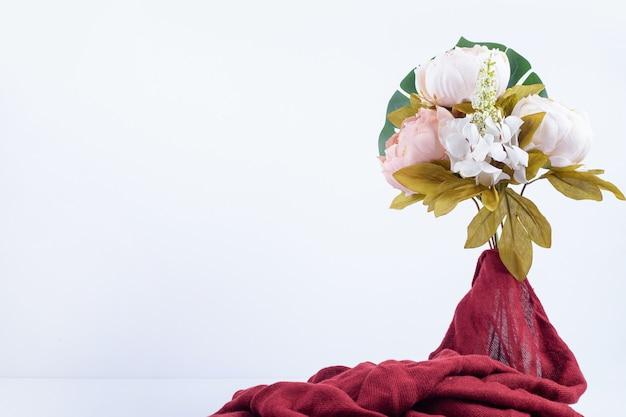 Bouquet de flores com pano vermelho.