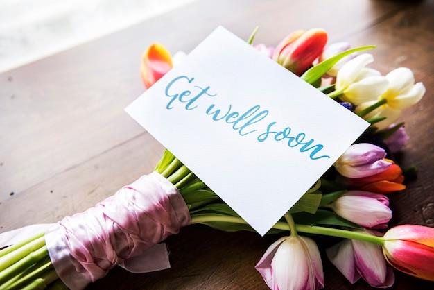Bouquet de flores de tulipas com get well soon desejando cartão