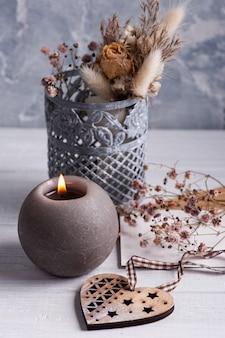 Bouquet de flores secas em vaso de lata na mesa de madeira branca, vela acesa e coração de madeira. copie o espaço para texto, para saudação, convite