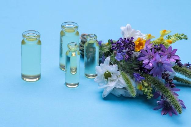 Bouquet de flores silvestres e frascos com óleo essencial em fundo azul