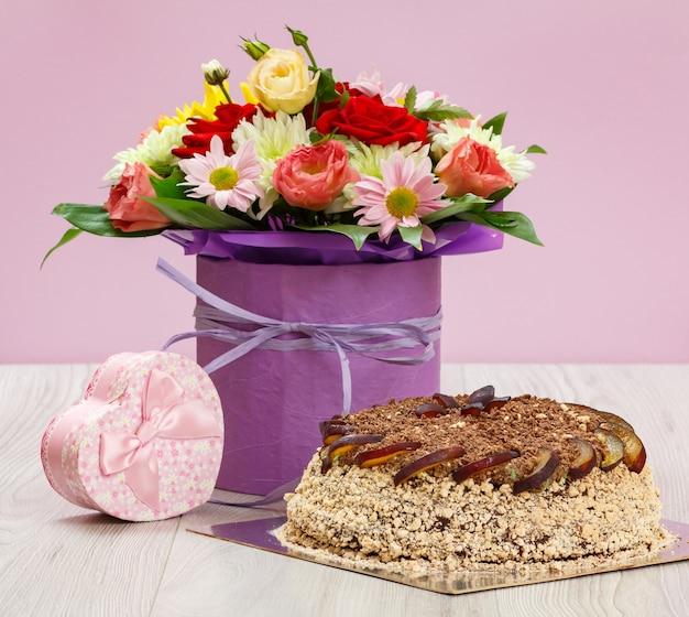 Bouquet de flores silvestres, um bolo de chocolate e uma caixa de presente rosa nas placas de madeira.