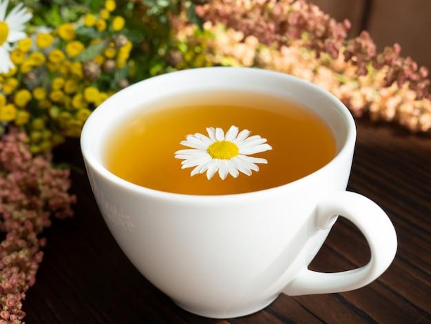 Bouquet de flores, uma xícara de chá na madeira