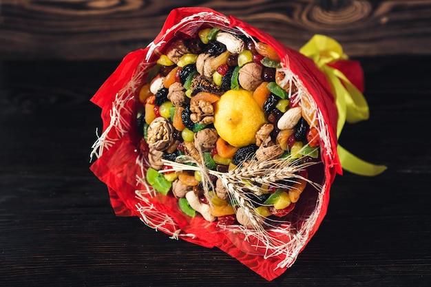 Bouquet de frutas secas, nozes, limão, em embalagem vermelha.