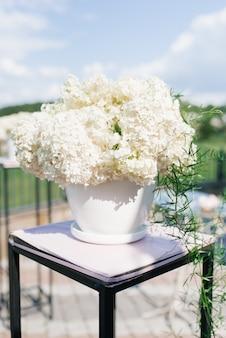 Bouquet de hortênsia branca em um vaso branco na decoração do registro de saída do casamento no casamento