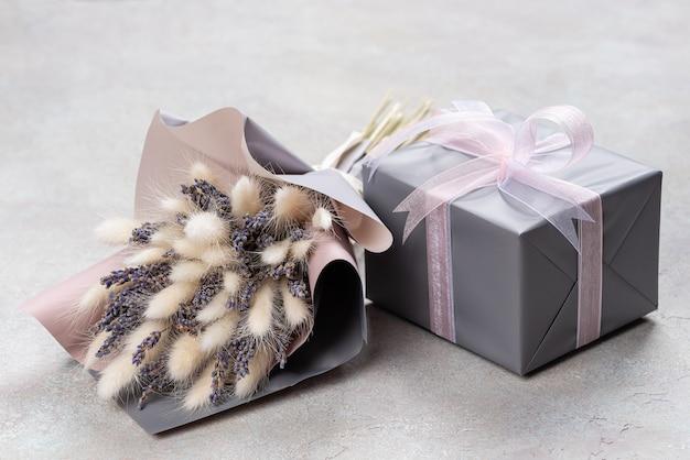 Bouquet de lavanda e lagurus com embalagem cinza-púrpura com uma caixa de presente em uma única cor.