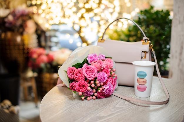 Bouquet de lindas flores cor de rosa e bolsa elegante em cima da mesa