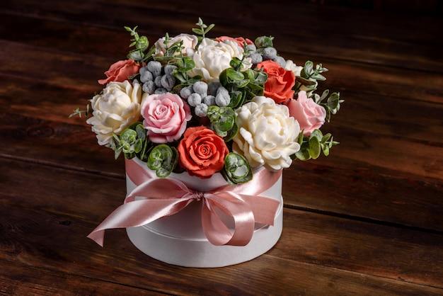 Bouquet de lindas flores rosas brilhantes em caixa de papelão cilíndrica para presente