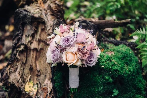 Bouquet de noiva close-up de rosas em rosa lilás sobre um fundo borrado de floresta e musgo, foco seletivo
