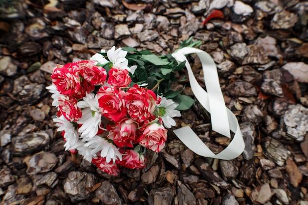 Bouquet de noiva de flores com uma fita em um fundo de madeira. elegante arranjo floral ao ar livre.