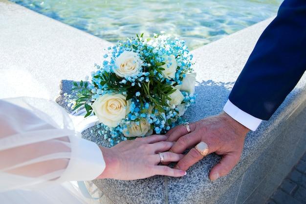 Bouquet de noiva de mãos dadas com anéis de casamento no fundo em um fundo de telhas de mármore, água e sol.