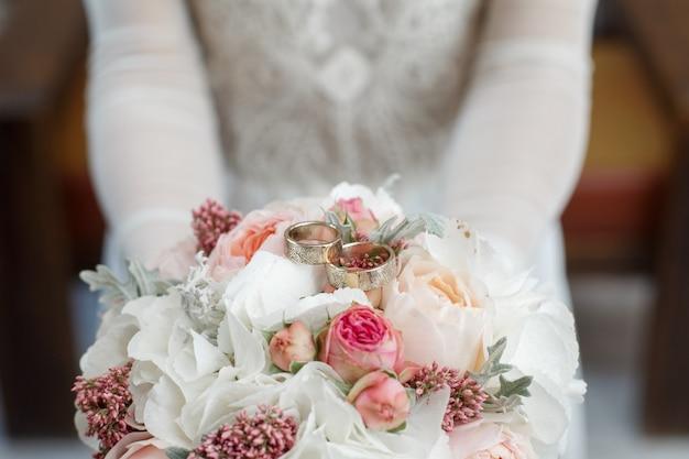 Bouquet de noiva de peônias brancas e rosas com alianças closeup. noiva possui alianças e buquê de noiva.