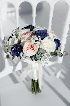 Bouquet de noiva de rosas brancas-de-rosa e azuis fica em uma cadeira antes da cerimônia, foco seletivo
