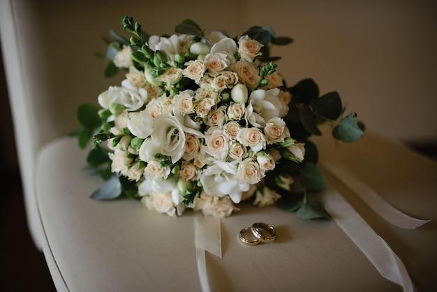 Bouquet de noiva e alianças de casamento em uma cadeira bege