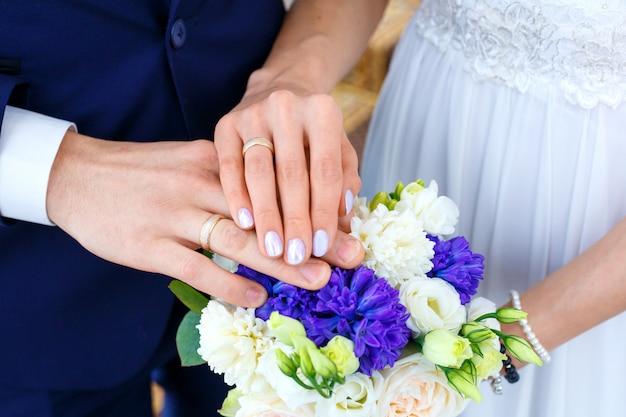 Bouquet de noiva e anéis de casamento nas mãos da noiva e do noivo