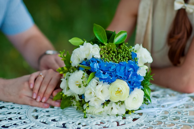 Bouquet de noiva e mãos da noiva e do noivo