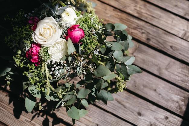Bouquet de noiva encontra-se numa superfície de madeira