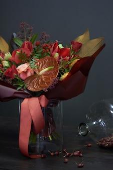 Bouquet de outono chique nas cores vermelhas em estilo vintage em um vaso de vidro e um pote enorme de roseira seca no escuro