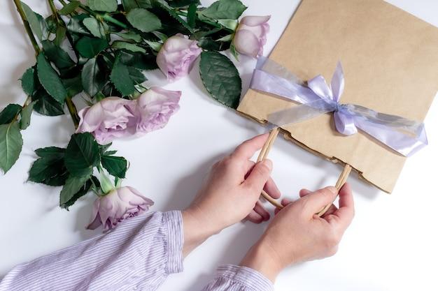 Bouquet de rosas violetas e mãos de mulher com sacola de compras em fundo branco, vista superior.