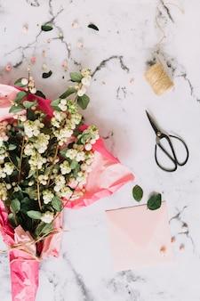 Bouquet de symphoricarpos albus; galhos snowberry comuns embrulhados em papel rosa com tesoura; bobina e envelope