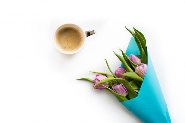 Bouquet fresco de cinco tulipas com uma xícara de café.
