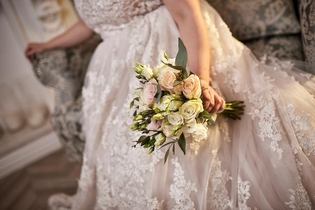 Bouquet nas mãos da noiva, mulher se preparando antes da cerimônia de casamento