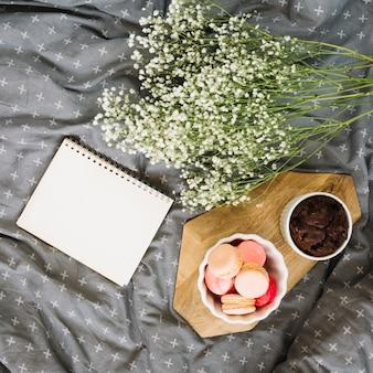 Bouquet perto de bloco de notas e sobremesas na cama