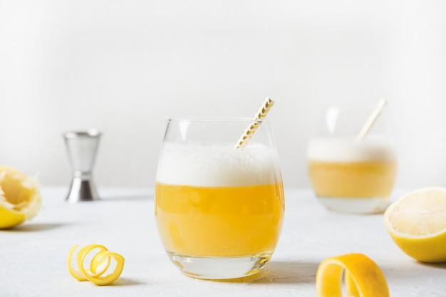 Bourbon com suco de limão, calda de açúcar e clara de ovo misturada em vidro
