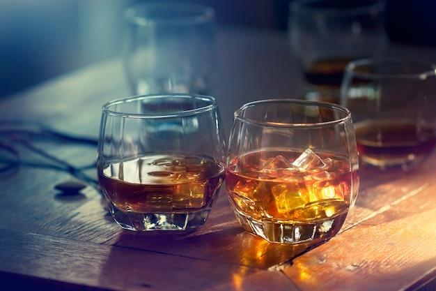 Bourbon de uísque em um copo com gelo no fundo colorido de mesa de madeira