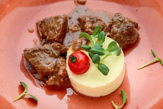 Bourguignon de carne rica e saborosa com purê de batatas em um prato na superfície de madeira