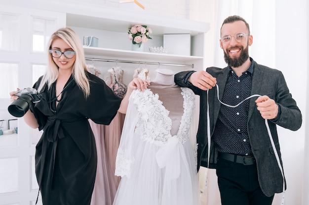 Boutique de vestidos de luxo. assistente pessoal e fotógrafo apresentando vestidos.