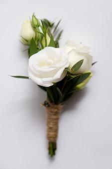 Boutonniere do noivo com rosas brancas e folhas verdes. parafernália de casamento e acessório.