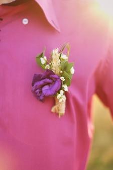 Boutonniere do noivo em uma camisa roxa