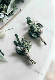 Boutonnieres em uma mesa de mármore branco